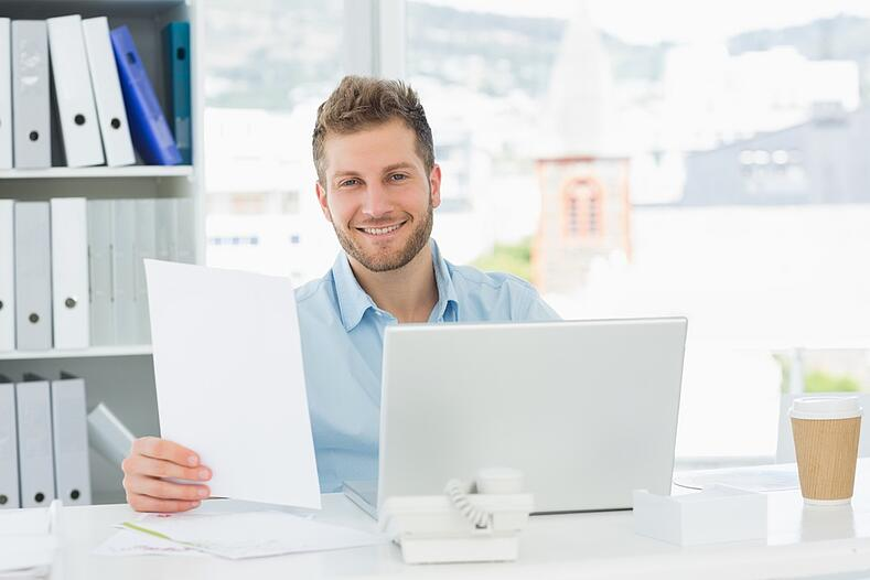 Handsome man working at his desk on laptop smiling at camera in creative office