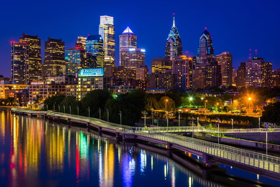 The Philadelphia skyline and Schuylkill River at night, seen from the South Street Bridge in Philadelphia, Pennsylvania.
