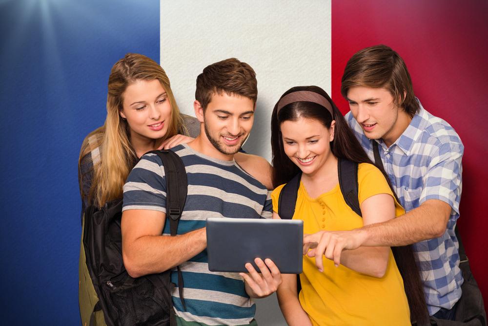 Students using digital tablet at college corridor against france national flag